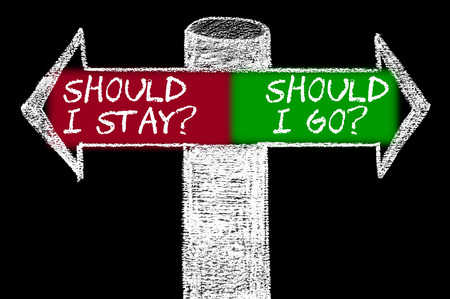 Opposite arrows with Should I Stay versus Should I Go. Hand drawing with chalk on blackboard Stok Fotoğraf