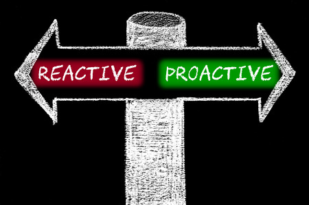reactive: Opposite arrows with Reactive versus Proactive. Hand drawing with chalk on blackboard.