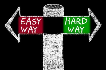 easy way: Opposite arrows with Easy Way versus Hard Way. Hand drawing with chalk on blackboard Stock Photo