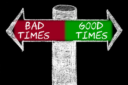 bad times: Opposite arrows with Bad Times versus Good Times. Hand drawing with chalk on blackboard