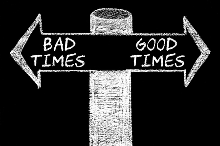 bad times: Opposite arrows with Bad Times versus Good Times. Hand drawing with chalk on blackboard. Choice conceptual image Stock Photo
