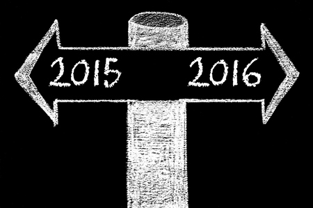 indecision: Opposite arrows with Year 2015 versus Year 2016. Hand drawing with chalk on blackboard. Choice conceptual image Stock Photo
