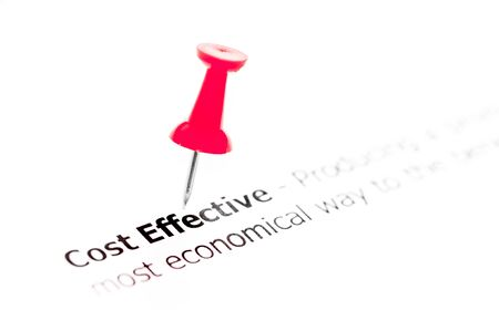 red pushpin: Words COST EFFECTIVE pinned on white paper with red pushpin, available copy space. Business Concept Stock Photo