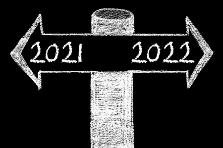 indecision: Opposite arrows with Year 2021 versus Year 2022. Hand drawing with chalk on blackboard. Choice conceptual image