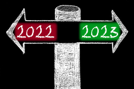 Opposite arrows with Year 2022 versus Year 2023. Hand drawing with chalk on blackboard. Choice conceptual image photo