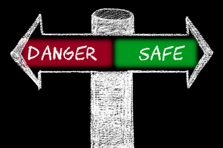 Opposite arrows with Danger versus Safe. Hand drawing with chalk on blackboard. Choice conceptual image photo