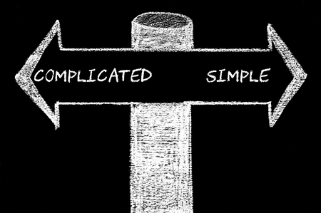 Opposite arrows with Complicated versus Simple.. Hand drawing with chalk on blackboard. Choice conceptual image photo