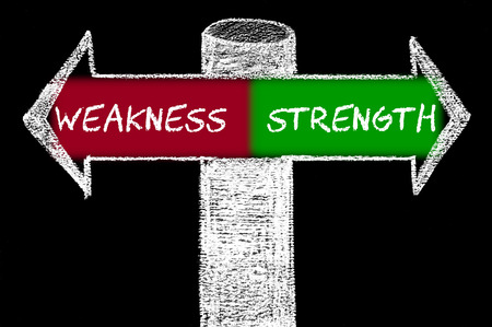 weakness: Opposite arrows with Weakness versus Strength. Hand drawing with chalk on blackboard. Choice conceptual image Stock Photo