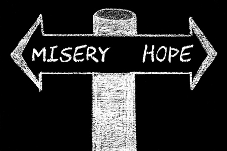 misery: Opposite arrows with Misery versus Hope. Hand drawing with chalk on blackboard. Choice conceptual image