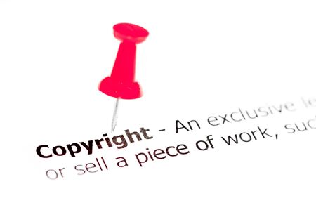red pushpin: Word COPYRIGHT pinned on white paper with red pushpin, available copy space. Business Concept