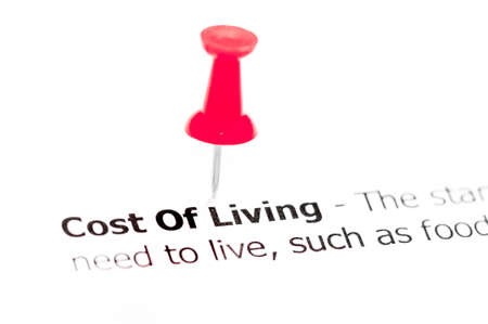 white pushpin: Words COST OF LIVING pinned on white paper with red pushpin, available copy space. Business Concept Stock Photo