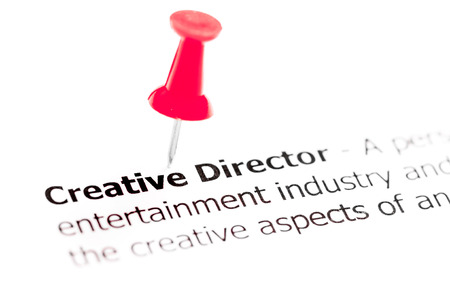 white pushpin: Words CREATIVE DIRECTOR pinned on white paper with red pushpin, available copy space. Business Concept