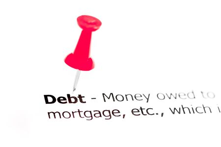 red pushpin: Word DEBT pinned on white paper with red pushpin, available copy space. Business Concept