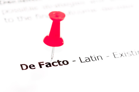 facto: Words DE FACTO pinned on white paper with red pushpin, available copy space. Business Concept