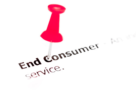 red pushpin: Words END CONSUMER pinned on white paper with red pushpin, available copy space. Business Concept