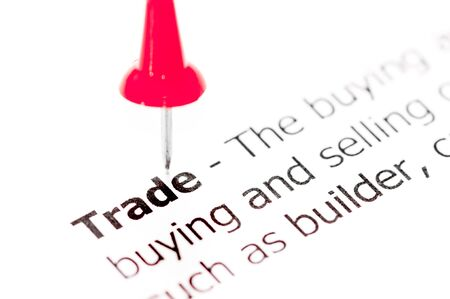 white pushpin: Word TRADE pinned on white paper with red pushpin, available copy space. Business Concept