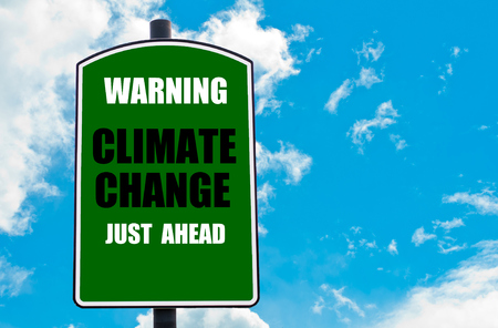 climate change: Warning Climate Change Just Ahead written on green road sign  against clear blue sky background. Concept image with available copy space Stock Photo