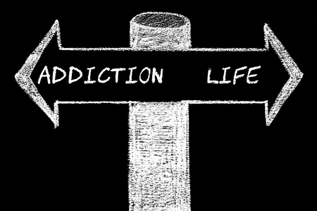 Opposite arrows with Addiction versus Life. Hand drawing with chalk on blackboard. Choice conceptual image