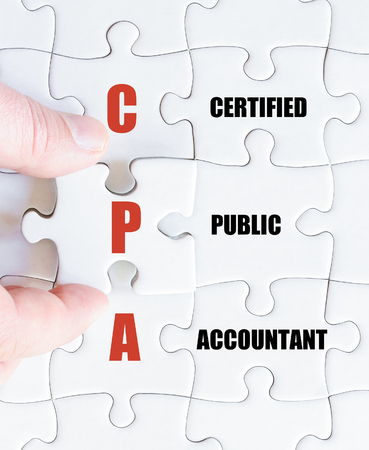 cpa: Hand of a business man completing the puzzle with the last missing piece.Concept image of Business Acronym CPA as Certified Public Accountant