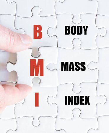 bmi: Hand of a business man completing the puzzle with the last missing piece.Concept image of Acronym BMI as Body Mass Index