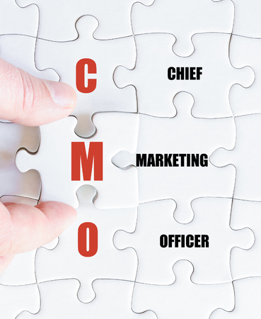 Hand of a business man completing the puzzle with the last missing piece.Concept image of Business Acronym CMO as Chief Marketing Officer Imagens