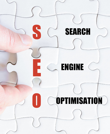 optimisation: Hand of a business man completing the puzzle with the last missing piece.Concept image of Business Acronym SEO as Search Engine Optimisation Stock Photo