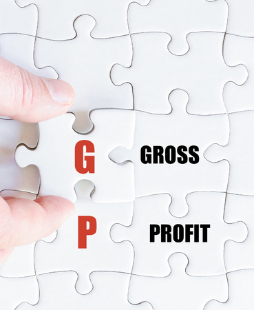 gp: Hand of a business man completing the puzzle with the last missing piece.Concept image of Business Acronym GP as Gross Profit