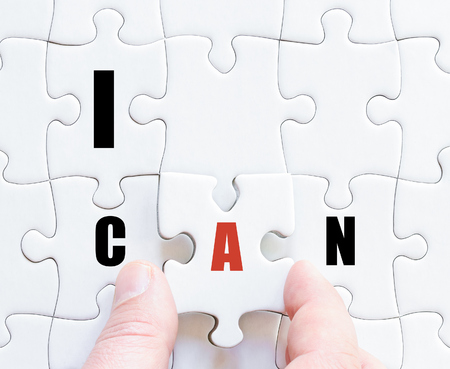 Hand of a business man completing the puzzle with the last missing piece.Concept image of puzzle board with motivational words I CAN