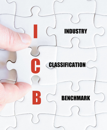classification: Hand of a business man completing the puzzle with the last missing piece.Concept image of Business Acronym ICB as Industry Classification Benchmark