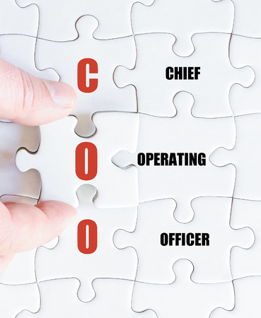 coo: Hand of a business man completing the puzzle with the last missing piece.Concept image of Business Acronym COO as Chief Operating Officer