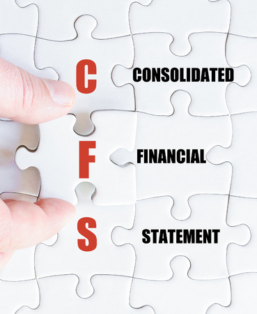 financial statement: Hand of a business man completing the puzzle with the last missing piece.Concept image of Business Acronym CFS as Consolidated Financial Statement