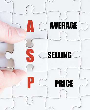 asp: Hand of a business man completing the puzzle with the last missing piece.Concept image of Business Acronym ASP as Average Selling Price Stock Photo
