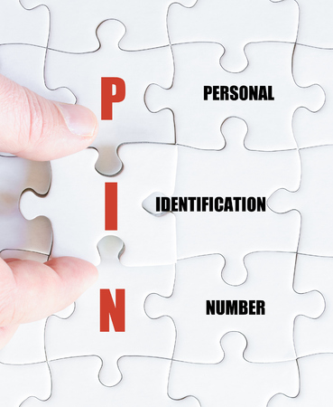 personal identification number: Hand of a business man completing the puzzle with the last missing piece.Concept image of Business Acronym PIN as Personal Identification Number Stock Photo