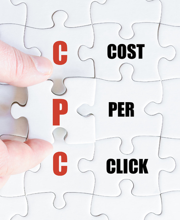 cpc: Hand of a business man completing the puzzle with the last missing piece.Concept image of Business Acronym CPC as Cost Per Click