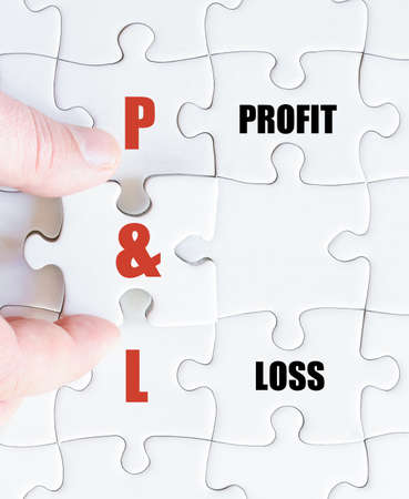 pl: Hand of a business man completing the puzzle with the last missing piece.Concept image of Business Acronym P&L as Profit and Loss Stock Photo