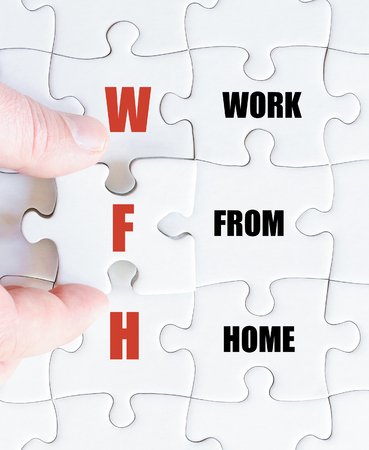work from home: Hand of a business man completing the puzzle with the last missing piece.Concept image of Business Acronym WFH as Work From Home Stock Photo