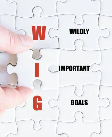 widely: Hand of a business man completing the puzzle with the last missing piece.Concept image of Business Acronym WIG as Widely Important Goals