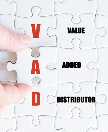 distributor: Hand of a business man completing the puzzle with the last missing piece.Concept image of Business Acronym VAD as Value Added Distributor