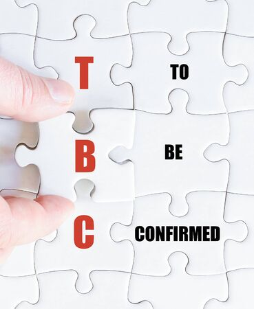 confirmed: Hand of a business man completing the puzzle with the last missing piece.Concept image of Business Acronym TBC as To Be Confirmed