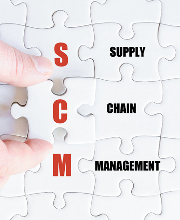 scm: Hand of a business man completing the puzzle with the last missing piece.Concept image of Business Acronym SCM as Supply Chain Management Stock Photo