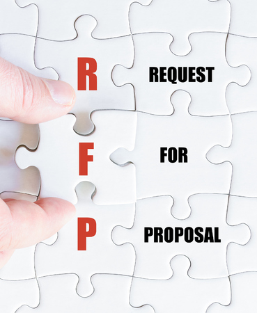 Hand of a business man completing the puzzle with the last missing piece.Concept image of Business Acronym RFP as Request For Proposal