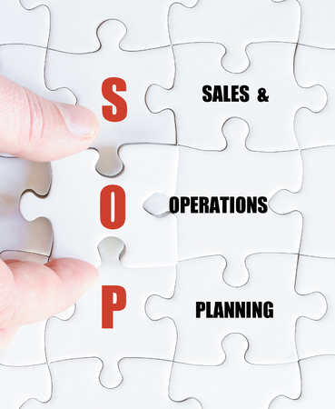 sop: Hand of a business man completing the puzzle with the last missing piece.Concept image of Business Acronym SOP as Sales and Operations Planning