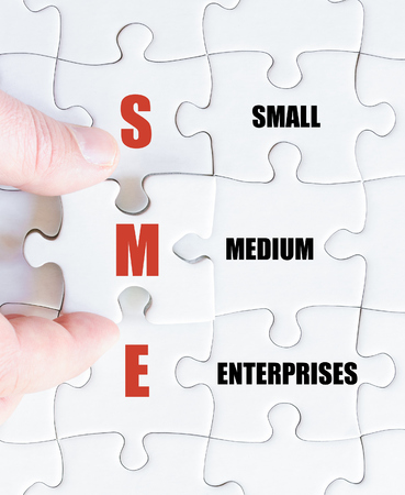 enterprises: Hand of a business man completing the puzzle with the last missing piece.Concept image of Business Acronym SME as Small Medium Enterprises Stock Photo