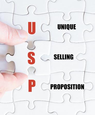 最後の行方不明の部分とパズルを完了するビジネスの男の手。ユニークな販売命題としてビジネスの頭字語 USP のコンセプト イメージ 写真素材