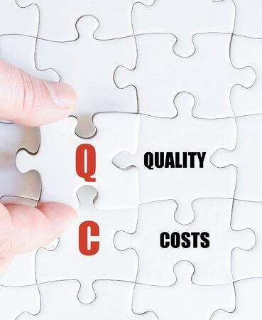 qc: Hand of a business man completing the puzzle with the last missing piece.Concept image of Business Acronym QC as Quality Cost Stock Photo