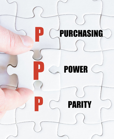 parity: Hand of a business man completing the puzzle with the last missing piece.Concept image of Business Acronym PPP as Purchasing Power Parity