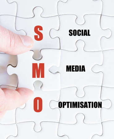 smo: Hand of a business man completing the puzzle with the last missing piece.Concept image of Business Acronym SMO as Social Media Optimisation