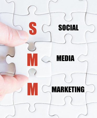 smm: Hand of a business man completing the puzzle with the last missing piece.Concept image of Business Acronym SMM as Social Media Marketing