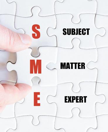 最後の行方不明の部分とパズルを完了するビジネス人の手。主題の専門家としてビジネスの頭字語中小企業のコンセプト イメージ