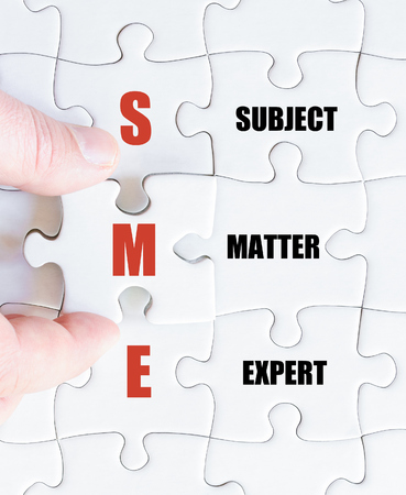 Hand of a business man completing the puzzle with the last missing piece.Concept image of Business Acronym SME as Subject Matter Expert